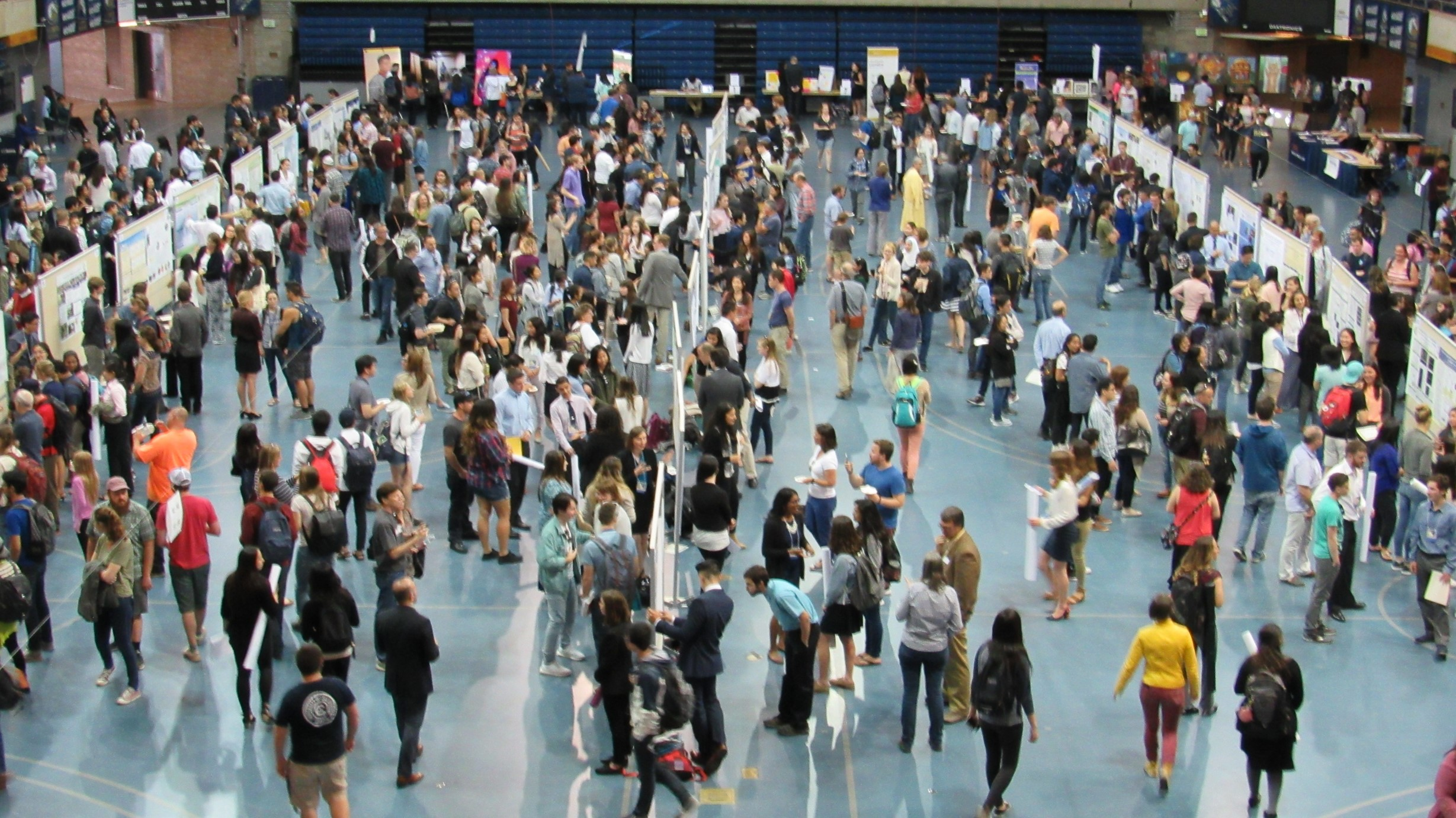 Wide photo of poster sessions on the floor of the ARC Pavilion showing many presenters, posters and participants with art exhibits in the back