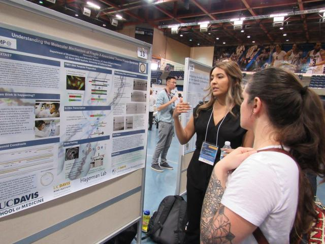 Poster presenter explaining research project to attendee during Undergraduate Research Conference