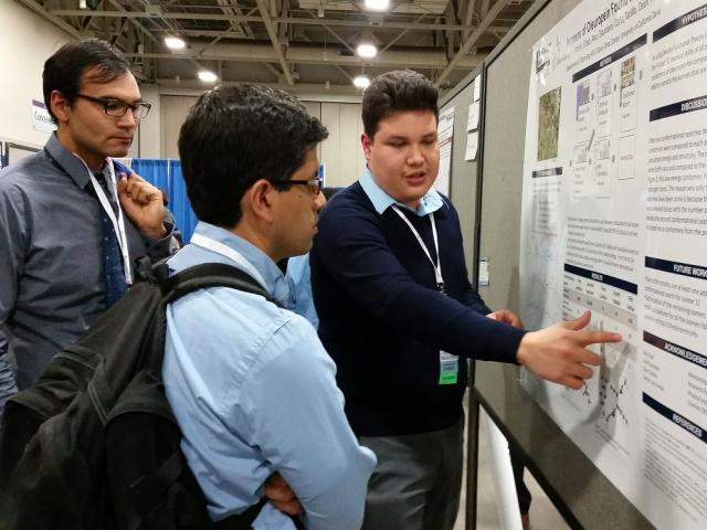 Student giving poster presentation at a conference