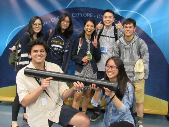 A group of undergraduate research students holding poster tube and posing in front of UC Davis URC conference back drop