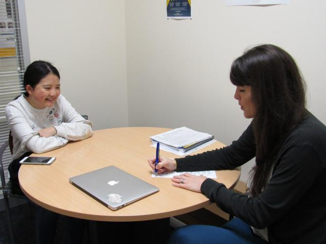 Undergraduate and graduate student seated at table during advising session