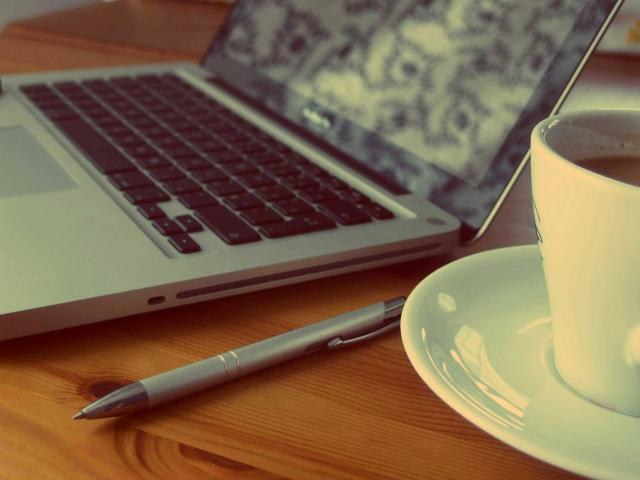 photo of laptop, pen and cup of coffee