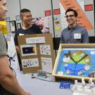 Undergraduate Researcher Christopher Ochoa and a graduate student explaining their fly research to visitors at the Bohart open house.