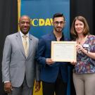 Photo of Mark Hanna, Mentor Mentee student alumnus accepting an award with Chancellor May on the left and Dean Carolyn Thomas on the right