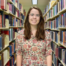 A photo of Megan west between library book shelves.